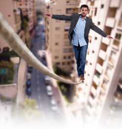 Man balancing on a rope between two towers